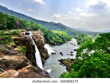 At the edge of the Athirapally Waterfall in Kerala, with a stunning view of the surrounding jungle and mountains - Kochi, India (Cochin)