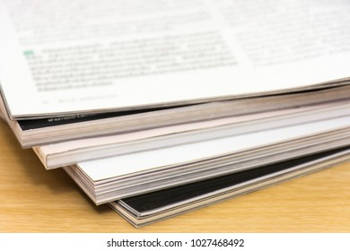 Edge book on the wooden table with blurred background. Stack magazines on wood desk background.