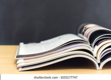 Edge book on the wooden table with blurred background. Stack magazines on wood desk background.   (selective focus )