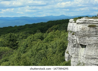 Edge of cliff view from the left with forest in the background and mountain ranges in the distance