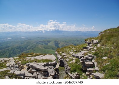 At the edge of crevice. Beautiful view of green valley, snowy Mount Elbrus and mountain chains of Greater Caucasus from Malyy Bermamyt Plateau. Nature and travel. Russia, Caucasus, Karachay-Cherkessia