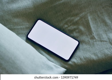 Edge to edge full screen smartphone with copy space on green bed sheet, cozy feeling.