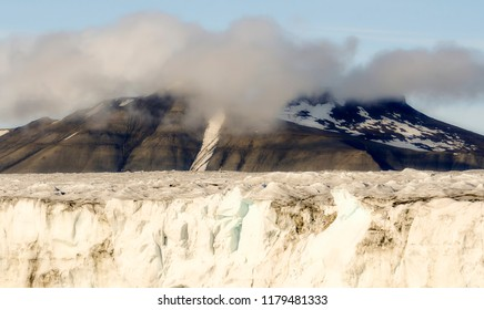 Edge of a Glacier with Ice Pack and Foggy, Cloudy, Snow Capped Mountains in the Background, on the Edge of the Arctic Ocean on the Coast of Spitsbergen Svalbard Archipelago in Northern Norway