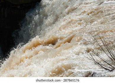 Edge of large powerful muddy brown waterfall rapids flowing and splashing into shadow, with branches on right.