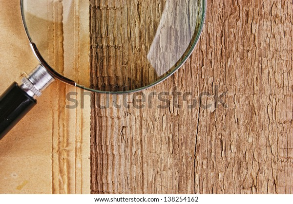 edge of the old newspaper and magnifying glass on a wooden background