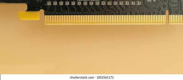 edge of pci express 16x connector of modern video card for personal computer on peach colored background, selective focus