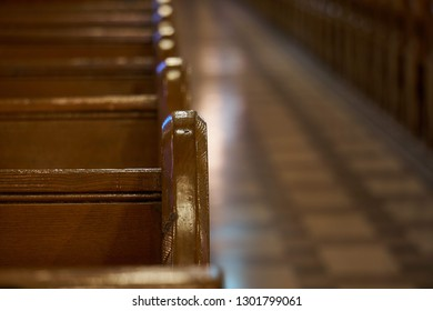 the edge of a pew looking back down the aisle of a church fading from in focus to out of focus