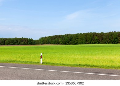 The edge of the road near the agricultural field, on the side of the established pillars with reflective elements for safety at night