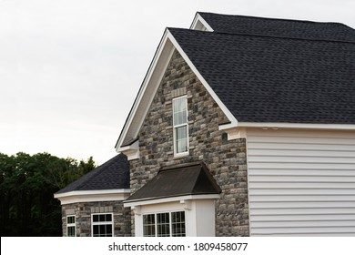 edge of roof shingles on top of the house dark asphalt tiles on the roof background color - Shutterstock ID 1809458077