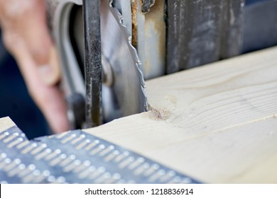 The edge of a saw blade cutting a notch out of a wood truss with shallow depth of field
