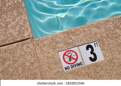 Edge of a swimming pool. 3 ft, no diving.