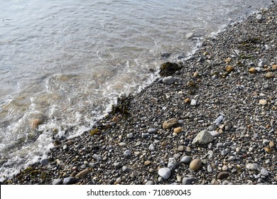 Edge of a wave gently rolling onto pebbles