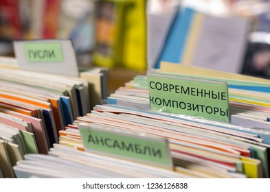 """Edges of multi-colored musical notebooks put in a row with inscriptions in Russian """"modern composers"""" and """"ensembles"""" on a blurred background."""