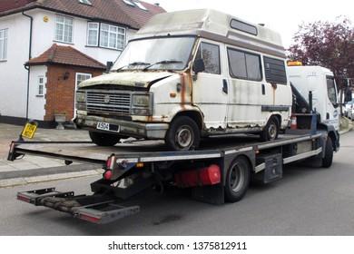 Edgware, London / UK - 04/16/2019: 1984 derelict Talbot Express camper van being loaded on to 2014 DAF LF 220 for scrap, Edgware, London, UK.