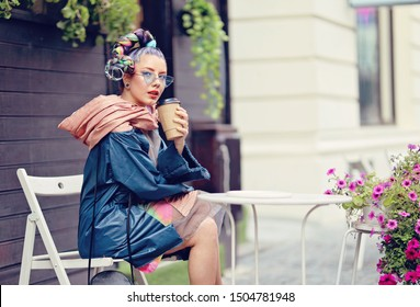 Edgy girl with extravagant look sitting at a coffee shop table. Crazy appearance on the boulevard in old town - Avant-garde fashion concept