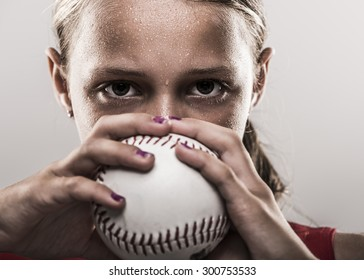 Edgy softball girl with sweat looking from behind a softball