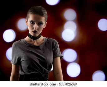 edgy young female model on dark background with bokeh. attitude with slicked back hair. rebel
