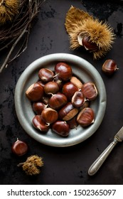 Edible chestnuts in a tin bowl on dark rustic background with a knife and chestnuts in a shell. Overhead view, flat lay