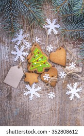 Edible Christmas decorations, gingerbread. White snowflakes with cookies on a wooden background, branches of spruce, fir. Rustic style. New-Year or Christmas greetings card.