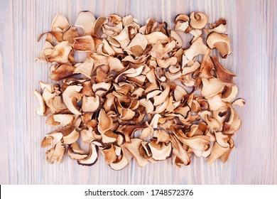 Edible dried mushrooms pile light wooden background close up top view, dry boletus edulis heap wood backdrop, chopped brown cap boletus, sliced penny bun, cep cut pieces, porcino, porcini, white fungi