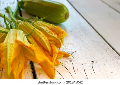 Edible flowers of courgettes and courgettes on a white table