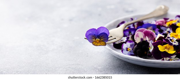 Edible flowers, field pansies, violets on white plate. Grey background. Copy space.