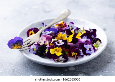 Edible flowers, field pansies, violets on white plate. Grey background. Close up.