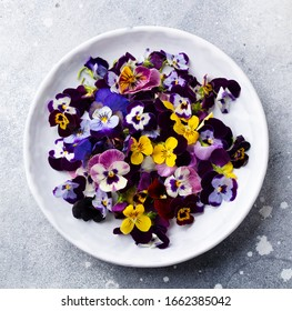 Edible flowers, field pansies, violets on white plate. Grey background. Close up. Top view.