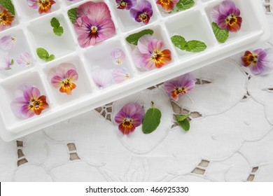 Edible flowers and mint in ice cubes tray on white vintage linen background