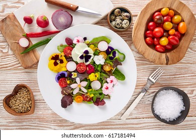 Edible flowers salad in a plate with ingredients
