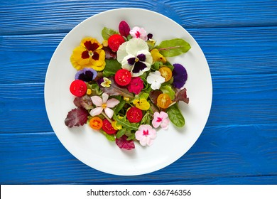Edible flowers salad in a plate on blue wooden table