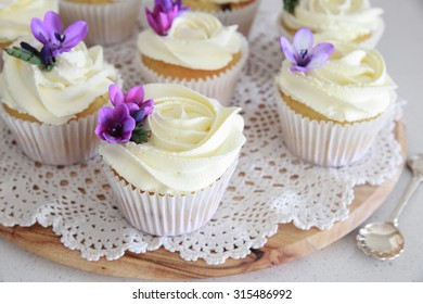 Edible purple freesia flowers on vanilla cupcakes with whipped cream frosting