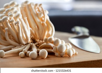 Edible shimei mushrooms and a knife on a chopping board in the kitchen
