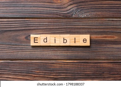 EDIBLE word written on wood block. EDIBLE text on cement table for your desing, concept.
