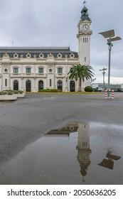 The Edificio del Reloj clock tower, port of Valencia, Spain, is reflected in a puddle of water