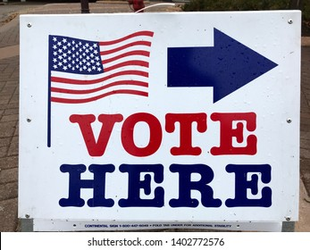 """Edina, MN/USA. November 6, 2018. A closeup of the """"Vote Here"""" sign outside of the voting place in the day of the US Primary Election in November."""