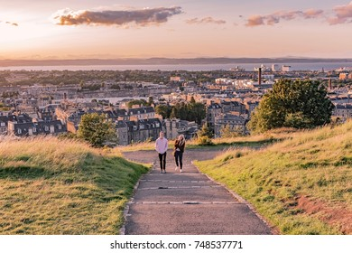 EDINBURG, ENGLAND - AUGUST 15, 2017 -  couple walking on Edinburgh Hill in Scotland at sunset