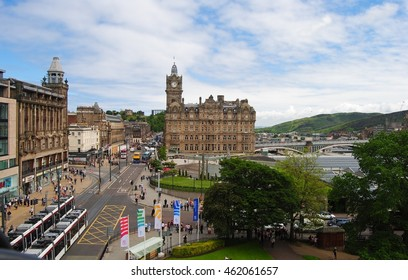 EDINBURG, GREAT BRITAIN - JUNE 14, 2014. View down Princes St in Edinburg, with historic building, including Balmoral Hotel, street traffic, people and vegetation.