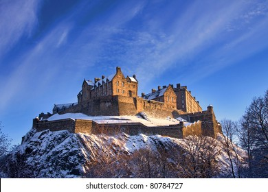 Edinburgh castle dusted with snow glows in the late afternoon winter sunset.