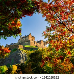Edinburgh Castle framed in autumn trees branches with green, orange and yellow leaves, Scotland, UK.