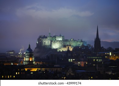 Edinburgh Castle, Scotland, at dusk in winter from the East.  On the left is the dome of the Talbot Rice Gallery (the public art gallery of The University of Edinburgh) and on the right the Hub.