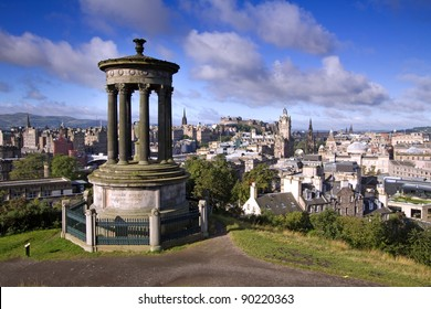 Edinburgh City and Castle, Scotland, from Calton Hill on a beautiful summer morning with the Dugald Stewart monument in the foreground and the Scott monument and Balmoral tower in the background.