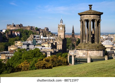 Edinburgh City and Castle, Scotland, viewed from Calton Hill on a beautiful summer morning with the Dugald Stewart monument in the foreground, Scott monument and Balmoral clock tower in background.