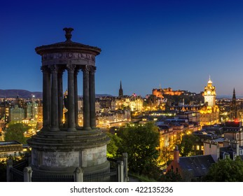 Edinburgh cityscape at night with the Dugald Stewart memorial in the foreground on Calton Hill, Scotland, UK