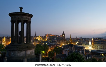 Edinburgh Cityscape at Sunset from Calton Hill with the Dugald Stewart Monument in front and the iconic Balmoral Hotel Clocktower in the background.