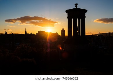 Edinburgh cityscape at sunset with the  iconic Dugald Stewart memorial in the foreground on Calton Hill, Scotland, UK