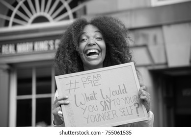 """Edinburgh, England - August 13 2017:  girl with sign in hand during Edinburgh Fringe Festival with written """"What would you say to your younger self"""""""