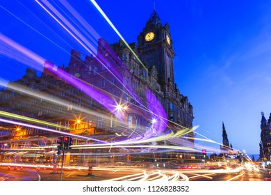 Edinburgh at night scene with Lights streak from high-sided vehicles on Princess street and Balmoral hotel on background