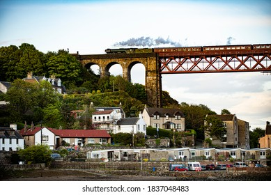 Edinburgh, North Queensferry / Scotland - 05/15/2015: The Flying Scotsman steam train crossing the Forth Rail Bridge with houses in North Queensferry below