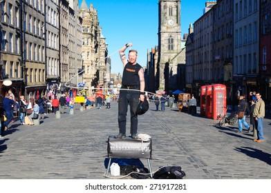 EDINBURGH, SCOTLAND -  18 APRIL, 2015: Street Artist known as Todd Various performs with ropes on the Royal Mile, Edinburgh